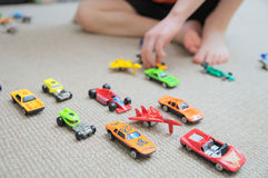 Pojke som spelar med bilsamlingen på matta Barnhandlek Trans.-, flygplan-, nivå- och helikopterleksaker för barn Royaltyfri Bild