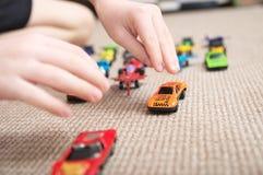 Pojke som spelar med bilsamlingen på matta Barnhandlek Trans.-, flygplan-, nivå- och helikopterleksaker för barn Royaltyfri Fotografi