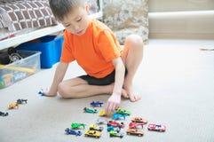 Pojke som spelar med bilsamlingen på matta Hem för barnlek Trans.-, flygplan-, nivå- och helikopterleksaker för barn Royaltyfri Fotografi