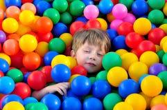 Pojke som spelar med bollar. arkivfoton