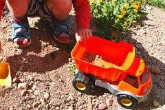 Pojke som spelar med den orange leksakbilen royaltyfria foton