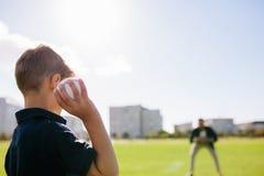 Pojke som spelar med en baseball på en parkera Royaltyfria Bilder