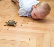 Pojke som spelar med en sköldpadda Arkivbild
