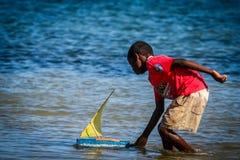 Pojke som spelar med ett fartyg Royaltyfri Foto