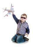 Pojke som spelar med ett flygplan Arkivbild