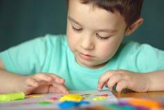 Pojke som spelar med färglekdeg royaltyfria foton
