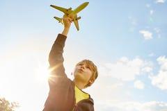 Pojke som spelar med flygplanet i hand royaltyfri bild