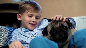 Pojke som spelar med hunden i huset på soffan arkivfilmer