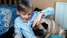Pojke som spelar med hunden i huset på soffan lager videofilmer
