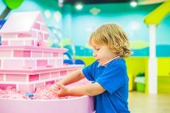 Pojke som spelar med kinetisk sand i förträning Utvecklingen av botmotorbegreppet Modigt begrepp för kreativitet Fotografering för Bildbyråer