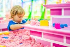 Pojke som spelar med kinetisk sand i förträning Utvecklingen av botmotorbegreppet Modigt begrepp för kreativitet Arkivfoto
