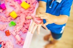 Pojke som spelar med kinetisk sand i förträning Utvecklingen av botmotorbegreppet Modigt begrepp för kreativitet Royaltyfria Foton