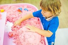Pojke som spelar med kinetisk sand i förträning Utvecklingen av botmotorbegreppet Modigt begrepp för kreativitet Arkivbilder