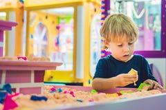 Pojke som spelar med kinetisk sand i förträning Utvecklingen av botmotorbegreppet Modigt begrepp för kreativitet Royaltyfri Foto