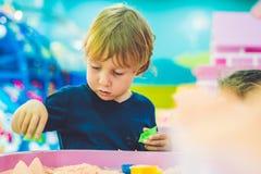 Pojke som spelar med kinetisk sand i förträning Utvecklingen av botmotorbegreppet Modigt begrepp för kreativitet Royaltyfria Bilder