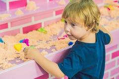 Pojke som spelar med kinetisk sand i förträning Utvecklingen av botmotorbegreppet Modigt begrepp för kreativitet Arkivbild