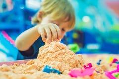 Pojke som spelar med kinetisk sand i förträning Utvecklingen av botmotorbegreppet Modigt begrepp för kreativitet Royaltyfri Bild
