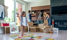 Pojke som spelar med leksakflygplanet, medan föräldrar packar upp Arkivbilder