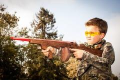Pojke som spelar med leksakgummibandvapnet Arkivbild