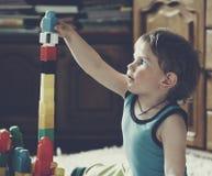Pojke som spelar med leksakkvarter och tegelstenar Arkivfoton