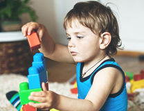 Pojke som spelar med leksakkvarter och tegelstenar Arkivbilder