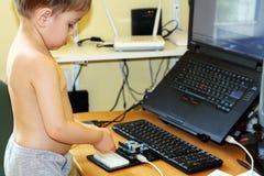 Pojke som spelar med mikrokontrolleren arkivbild