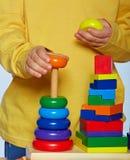 Pojke som spelar med pyramiden Arkivbild