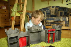 Pojke som spelar med riddares slott Arkivbild