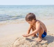 Pojke som spelar med sand i stranden Arkivbilder
