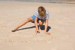 Pojke som spelar med sand, medan huka sig ned på stranden Royaltyfria Foton