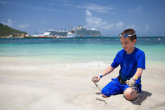 Pojke som spelar med sand på stranden Royaltyfria Bilder