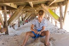 Pojke som spelar med sand under koja Royaltyfri Fotografi
