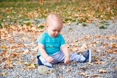 Pojke som spelar med sidor i höst royaltyfria foton