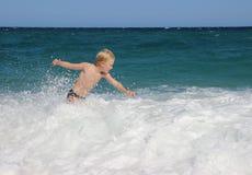 Pojke som spelar med vågorna av havet Arkivfoto
