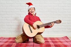 Pojke som spelar musik på gitarren som är iklädd en röd woolen tröja och santa hatt som sitter på en röd rutig filt, vit nolla fö Arkivfoton