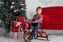 Pojke som spelar nära julgranen Royaltyfri Foto