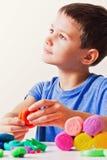 Pojke som spelar och skapar från att modellera lera eller plasticine arkivbilder