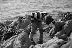 Pojke som spelar och undersöker i tidvattens- tips nära havet Royaltyfria Bilder