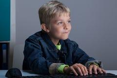 Pojke som spelar på bärbara datorn Arkivbild