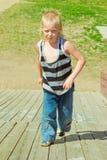 Pojke som spelar på en träglidbana Royaltyfri Bild