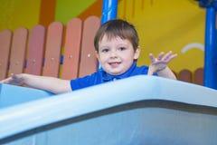Pojke som spelar på lekplatsen, i labyrinten för barn` s Glidbana för barn` s royaltyfria foton