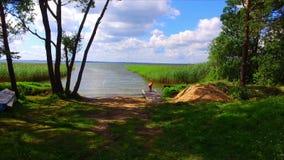 Pojke som spelar på sjökust för grönt gräs arkivfilmer