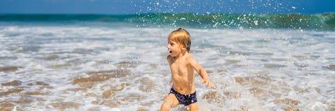 Pojke som spelar på stranden i vattenBANRET, LÅNGT FORMAT fotografering för bildbyråer
