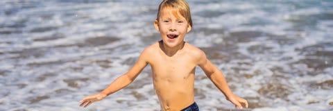 Pojke som spelar på stranden i vattenBANRET, LÅNGT FORMAT arkivbilder