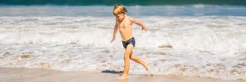Pojke som spelar på stranden i vattenBANRET, LÅNGT FORMAT royaltyfri foto