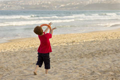 Pojke som spelar på stranden med en frisbee Arkivbild