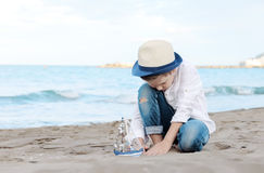 Pojke som spelar på stranden med ett skepp Sommarsemester och lopp Royaltyfri Foto