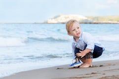 Pojke som spelar på stranden med ett skepp Sommarsemester och lopp Arkivfoton
