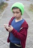 Pojke som spelar på telefonen Royaltyfria Bilder