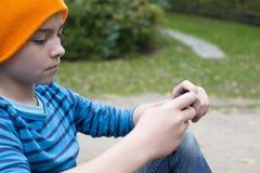 Pojke som spelar på telefonen Arkivfoton